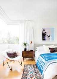 bright boho inspired bedroom with a gray linen headboard aztec