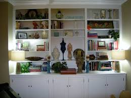 white wooden bookshelves with some doors connected by twin table