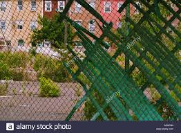 rowhomes in the ghetto viewed through a chainlink fence stock