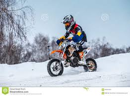 snow motocross bike closeup little boy racers motorcycle rides through snow covered