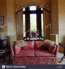 patterned red sofa in front of tall window in country drawing room