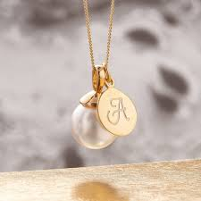 monogram charm pearl necklace in gold with monogram charm by claudette worters
