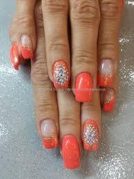 orange gel polish with glitter and swarovski crystal nail art