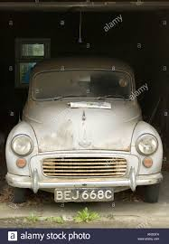 old grey morris minor 1000 car in garage covered in dust stock
