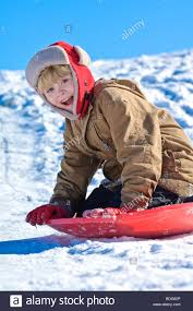 an excited boy sleds a snowy hillside in jefferson wisconsin