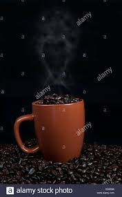 cup of coffee beans sitting on top of coffee beans with steam