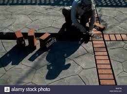mason lays red clay bricks between stamped concrete slabs