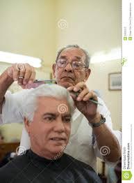 old barber cutting hair to client in barber shop stock photography