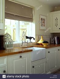 Beige Linen Blind On Window Above Belfast Sink In Modern Kitchen - Kitchen with belfast sink