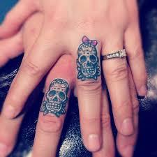 two sugar skull on finger