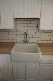 white subway tile backsplash with beige grout floor decoration