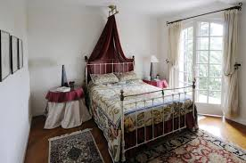 amazing country bedroom with maroon bed canopy and iron bed frame