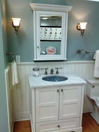 white wooden vanity with round blue sink and marble top on