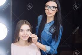 looking for makeup artist looking makeup artist holding a cotton disc stock photo