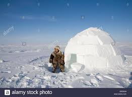 a young inuit boy stands outside of an igloo in layers of warm