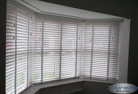 white wooden blinds with tapes in a bay window harmony blinds of