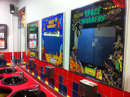 the mirrors in this bathroom were surrounded by old arcade game
