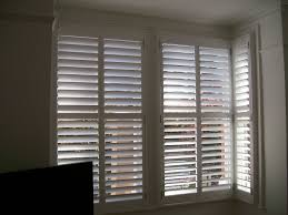 interior shutters photo with blackout blinds on windows