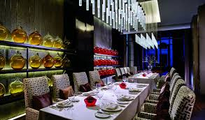 zest the ritz carlton tianjin room with two long dining tables shelves lined with glass vases and two table