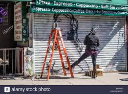 Mural Artist by Spray Paint Mural Artist Painting A Picture Of A Woman On A Store