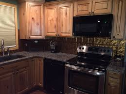 natural stain knotty alder kitchen cabinets gold tile backsplash