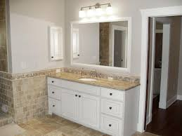 gold bathroom mirror with beige stone floor bathroom traditional