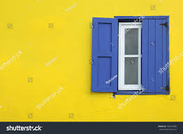 colorful yellow house blue shutters window stock photo 105074960