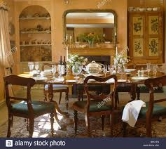 antique chairs at table set for lunch in country dining room with