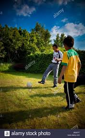 father and son playing soccer in the backyard netherlands stock
