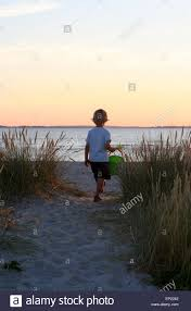 boy walking to the beach with a plastic bucket and shovel