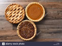 three pies for thanksgiving on a wood surface the desserts include