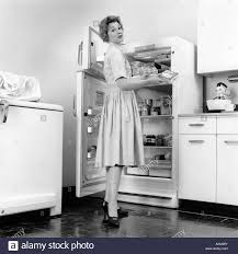 femme dans la cuisine 1950 femme debout dans la cuisine d un réfrigérateur banque d images