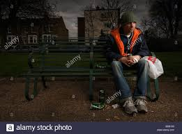 a man sits on a london park bench drinking lager stock photo
