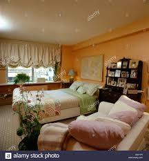cream festoon blind and orange walls in eighties bedroom with