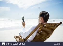 Chairs On A Beach Man Sitting In Chair On Beach Using Cell Phone Rear View Stock