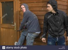 Burglars by Two Burglars Breaking Into A Shed Using A Jemmy Crowbar Posed
