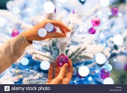 woman at home decorating christmas tree close up hands stock