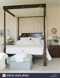 cream drapes and linen on four poster bed in country bedroom with