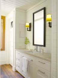bright cottage bathroom features wall to ceiling white paneling