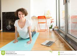 Livingroom Yoga by Woman Doing Yoga With Online App On Computer In Her Living Room
