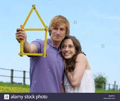 young couple holding folding ruler shaped as house planning new