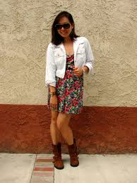brown moto boots spinning threads white denim jacket floral dress and motorcycle