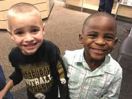two boys one white and one black get same haircut to trick