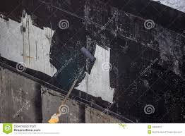waterproofing worker painting exterior concrete wall with tar i