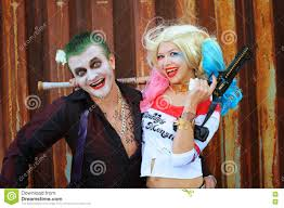 cosplayer in harley quinn costume and man in joker costume