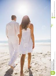 attractive couple holding hands and walking to the water stock