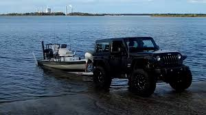 jeep offroad trailer man loading boat onto trailer and then pulls it out of the water