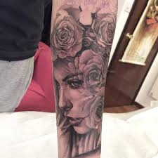 grey ink face with roses tattoo on forearm
