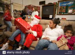 a volunteer santa claus distributes donated gifts to low