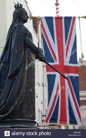 low angle view of a statue of queen victoria near the british flag
